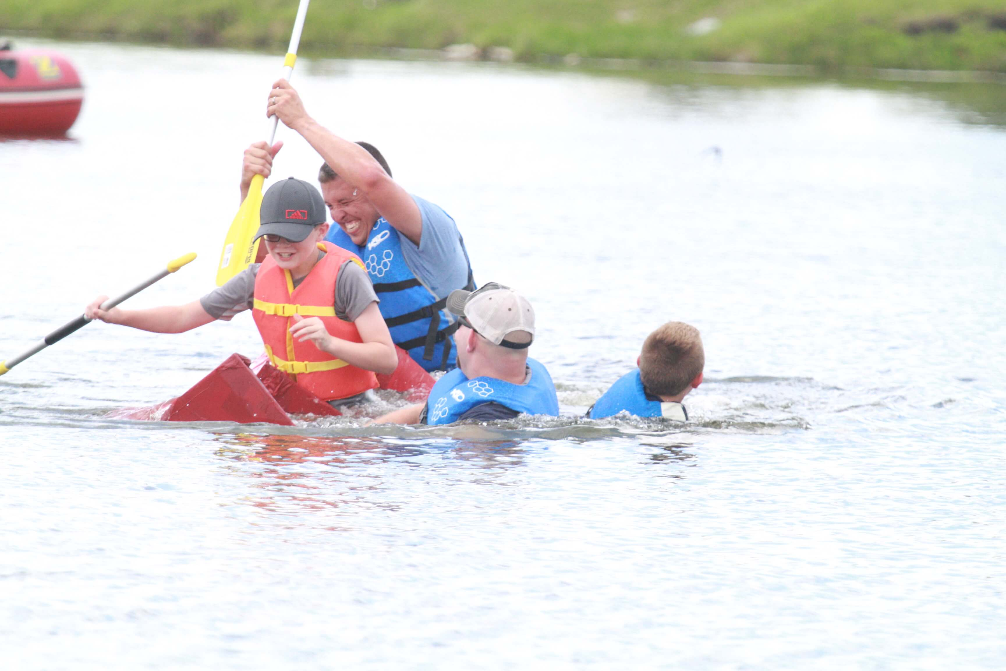 4 Participants in the Boat Regatta event struggle to keep their cardboard boat afloat. While wearing lifejackets, the team struggles with a submerging boat.