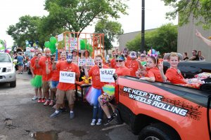 The participants in the first place winner of the Grand Parade Float decorating contest pose for a photo near their float, which is decorated in orange and is carrying a 'human zoo cage'.