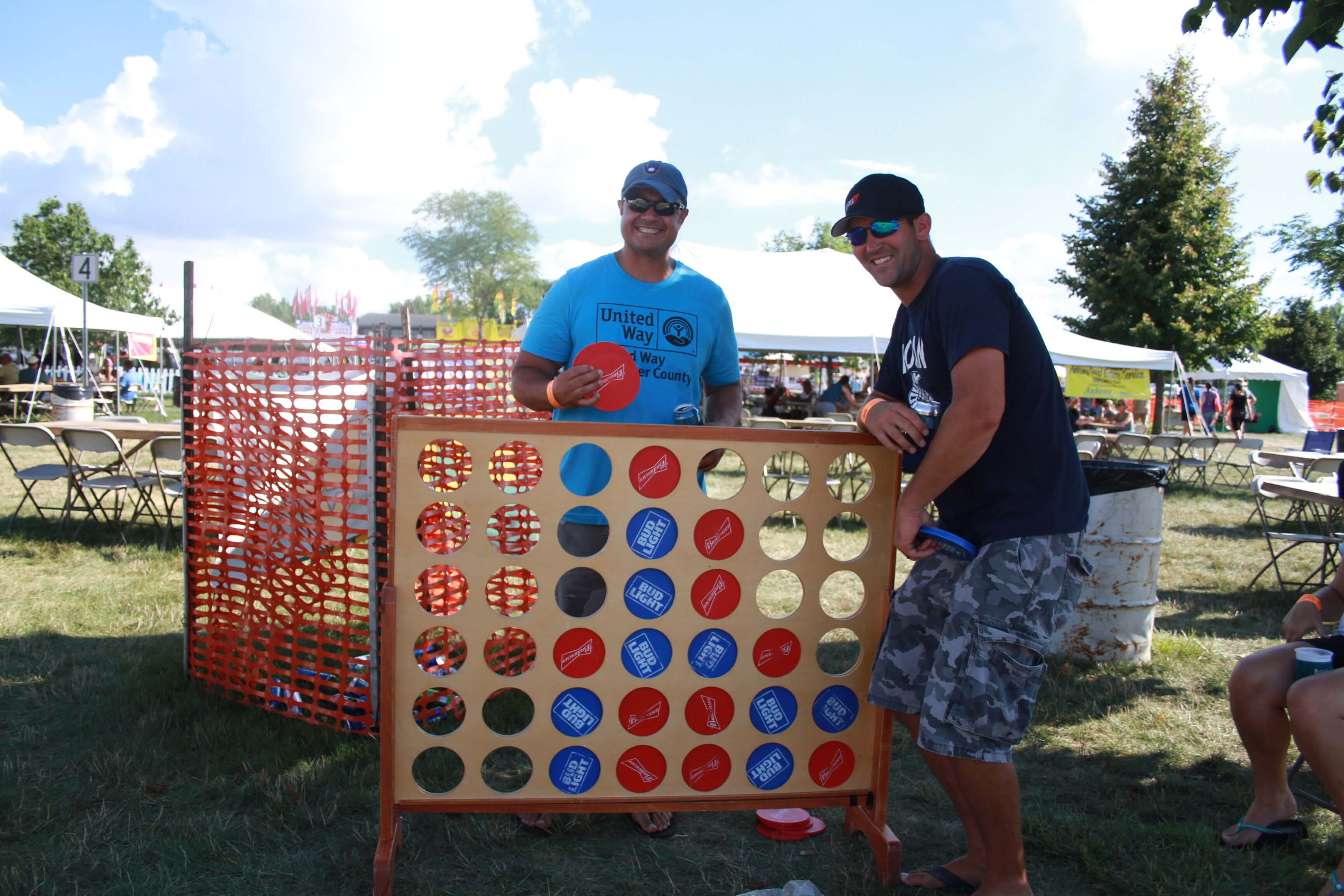 Two adults participate in Grown Up Game Day with a game of jumbo connect 4.