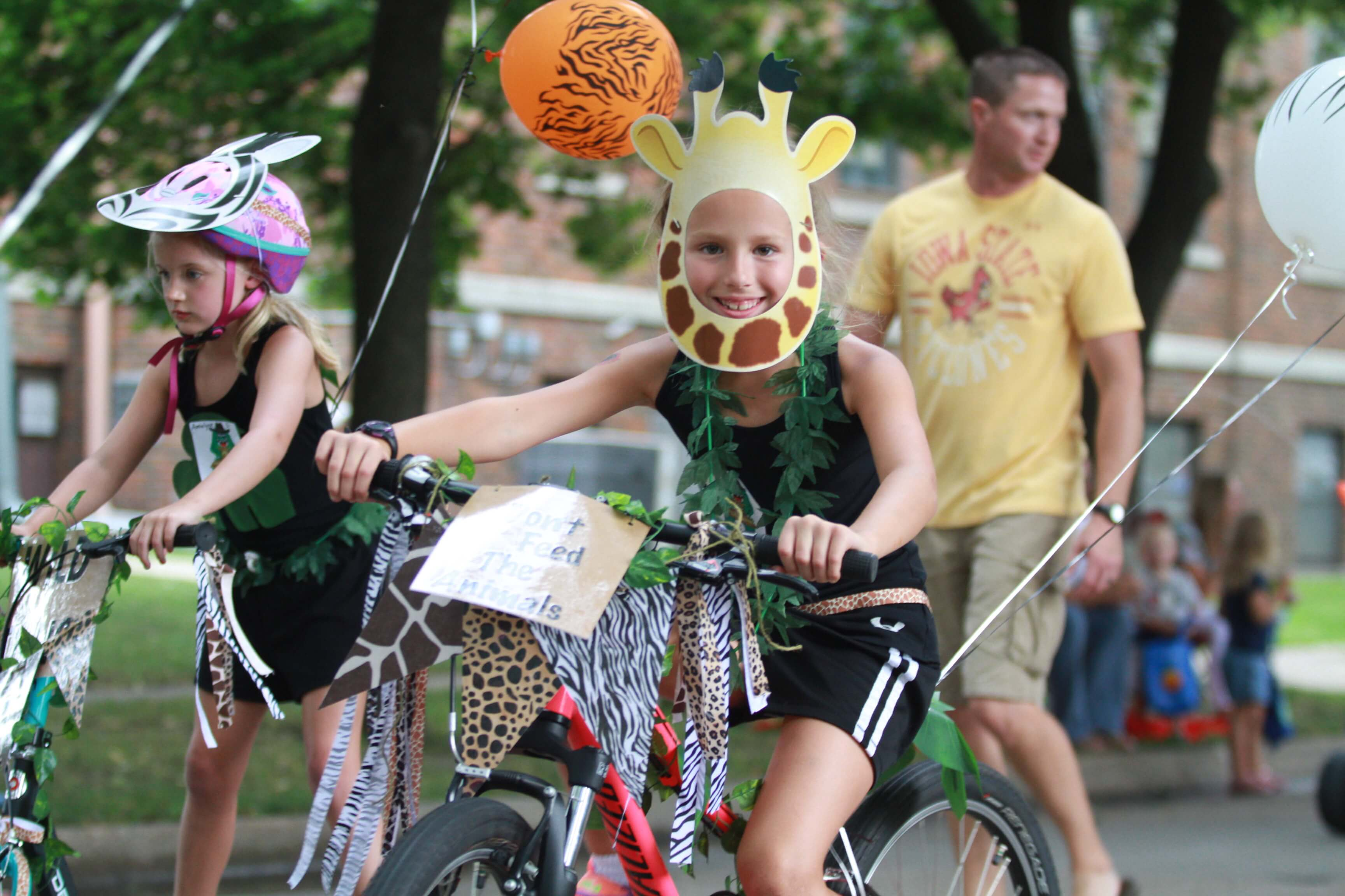 Two girls participate in the Kiddie Parade on bikes with their helmets decorated as a Giraffe and a Zebra.