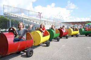 Kids wave from a ride on a barrel train. The train is made of hollowed-out and cut barrels with wheels, seats, and steering wheels.