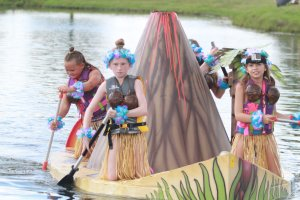 Four girls paddle their cardboard boat, which is shaped into a volcano with a platform for them to kneel on. The girls are wearing coconut bras over their life jackets in accordance with the theme.