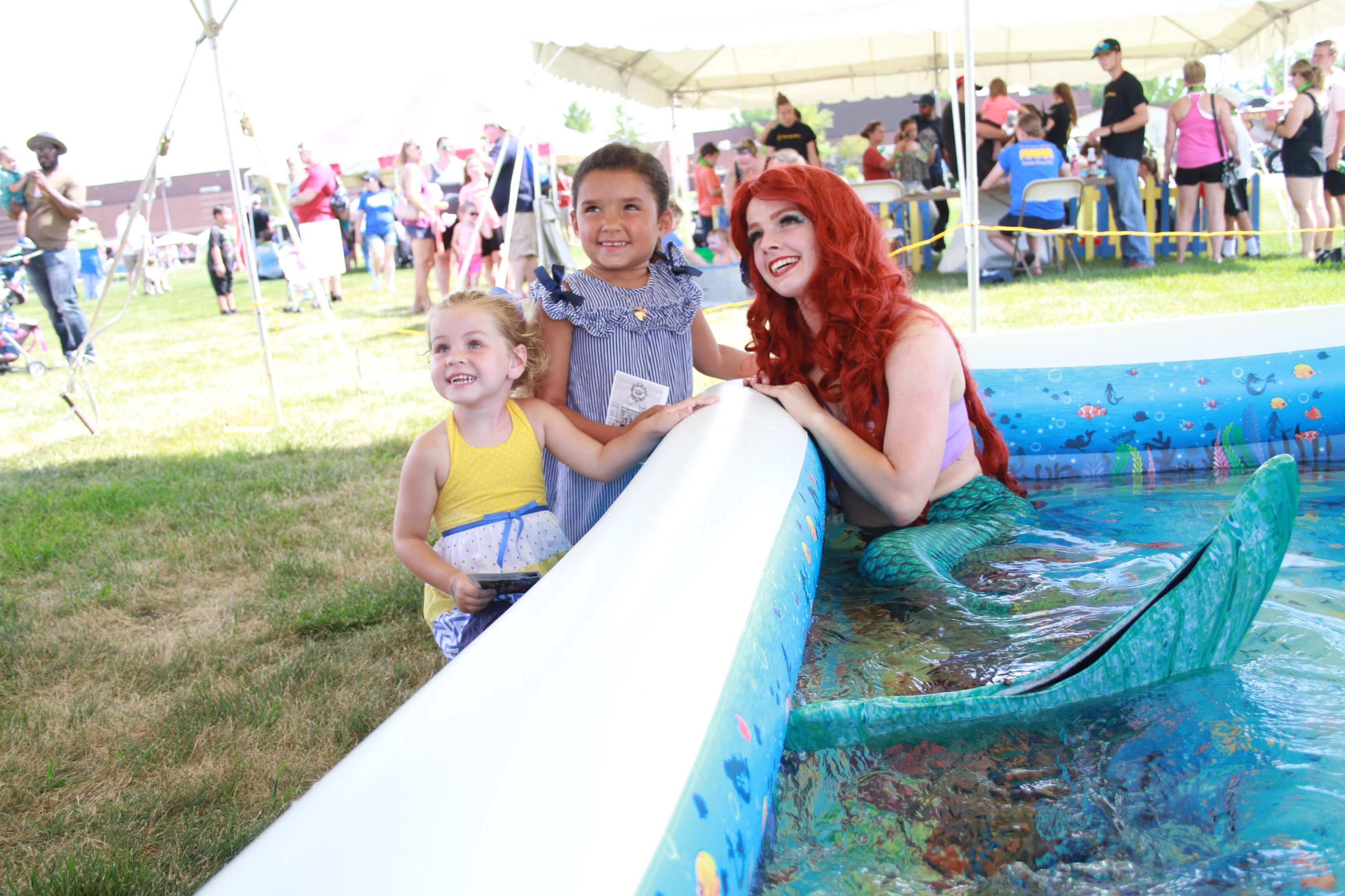 Two little girls pose for a picture next to a worker dressed up as Ariel from The Little Mermaid in a swimming pool.