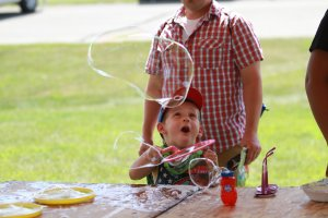 A young boy plays with a bubble wand as an adult stands behind him during Family Fun Day at SummerFest.