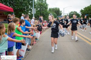 Centennial Cheerleaders give high fives to onlookers at the Grand Parade.