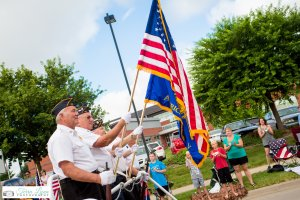 Older men in uniform bear flags at the front of the Ankeny SummerFest Grand Parade.