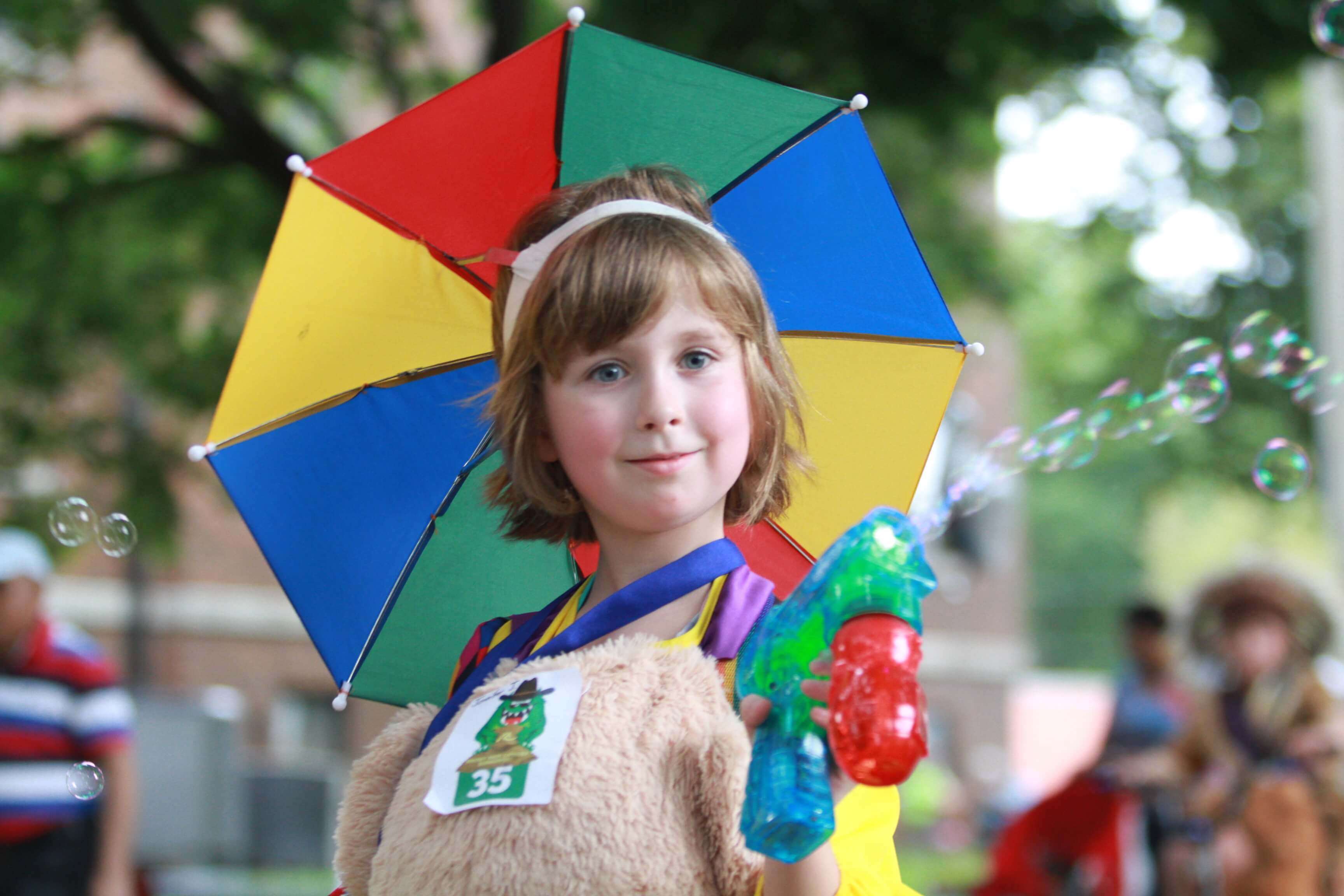 A little girl wearing a rainbow umbrella hat shoots bubbles out of a bubble gun while walking in the Kiddie Parade.